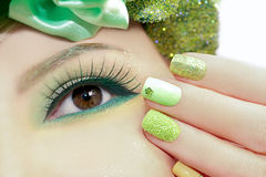 Green makeup and nail Polish. Green makeup and nail Polish with sparkles and rhinestones of different shapes Royalty Free Stock Photos