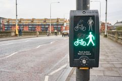 Green man signal at a typical pedestrian crossing in UK. A `green man` signal, typical to UK, informs pedestrian that road can be crossed safely Stock Photo