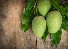 Green mango on wood background. Tropical fruit Royalty Free Stock Photography