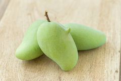 Green Mango on a wooden table Royalty Free Stock Image