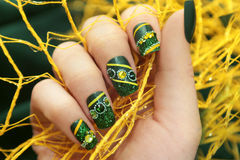Green manicure square shape . Green manicure square shape nail glitter,rhinestones and yellow lines a close-up Stock Images