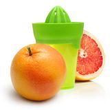 Green manual juicer and citrus fruit Royalty Free Stock Photo
