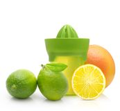 Green manual juicer and citrus fruit Royalty Free Stock Photos
