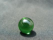 Transparent and green glass Marble. A green marble made of glass. Transparent and alone stock images