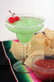 Green margarita with chips and salsa. Green margarita with two cherries and chips and salsa on a Mexican serape Stock Photos