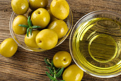 Green marinated olives, olive oil. Green marinated olives, olive oil on a wooden table Stock Photo