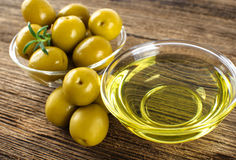 Green marinated olives, olive oil. Green marinated olives, olive oil on a wooden table Stock Image
