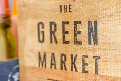 Green market sign on wooden background Royalty Free Stock Photos