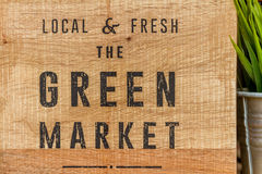 Green market sign on wooden background Royalty Free Stock Photo