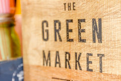 Green market sign on wooden background Royalty Free Stock Photography