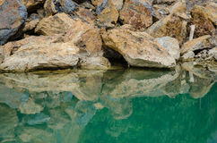 Green Marsh and Reflection of Stones. The Stone Reflect On Clear Water In The Green Marsh Stock Photo