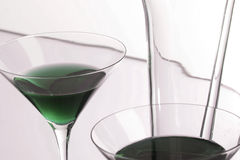 Green Martini Envy. Green martini. Stemware and pitcher. Lot of white. Close-up and a bit abstract. High tech look royalty free stock images