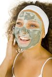 Green mask on face. Young woman putting on face green purifing mask. She's on white background Royalty Free Stock Image