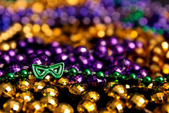 Green Mask Mardi Gras Beads. Green mask-shaped Mardi Gras beads with purple and gold beads