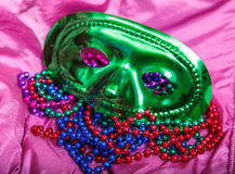 Green Mask and Mardi Gras Beads on Purple Background Stock Image