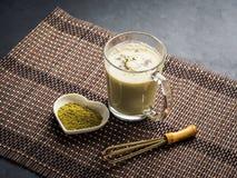 Green matcha tea latte mug on dark background. With powder and whisk royalty free stock photos