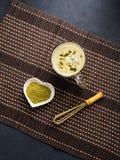 Green matcha tea latte mug on dark background. With powder and whisk stock photo