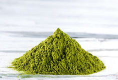 Green matcha tea powder. Heap of green matcha tea powder on white weathered wooden background Stock Photos