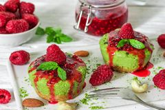 Green matcha vegan raw cakes with raspberries, jam mint and nuts. healthy delicious food royalty free stock photos