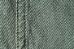 Green material - denim jeans. Detail of a green denim fabric with sew Stock Images