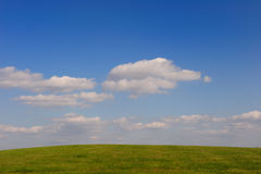 Green meadow. And the blue sky with white clouds Royalty Free Stock Photo