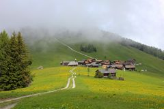 Green Meadow And Village Obermutten On A Foggy Summer Day Royalty Free Stock Images