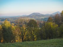 Green meadow with autumn colorful forest and trees and hills bef Stock Photos