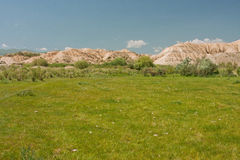 Green meadow on the background of a mountain range Royalty Free Stock Photo