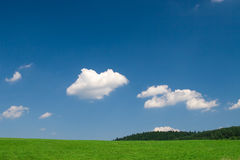 Green meadow with blue sky. Green field and blue sky with cumulus clouds stock photo