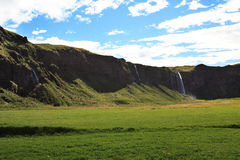 Green Meadow and Cliffs of Iceland. Flat, green meadow in Iceland, ringed by high, sheer mountain cliffs with a waterfall in the background Royalty Free Stock Image