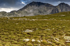 Green meadow and clouds over Kamenitsa peak Royalty Free Stock Image