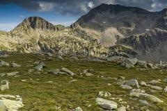 Green meadow and clouds over Kamenitsa peak, Pirin Mountain, Bulgaria Royalty Free Stock Photos
