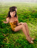 Green meadow gold dress. Cute Latin American female sitting on a green meadow dressed in a gold dress and shoes Stock Image