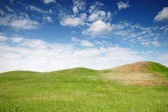 Green meadow, hills and blue sky Stock Images