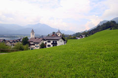 The green meadow with the houses in the mountains. Stock Photo