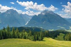 Green meadow, mountain ridge under blue sky. Bright green meadow, mountain ridge under blue sky. Alpine summer scenery in Bavaria, Germany Royalty Free Stock Image