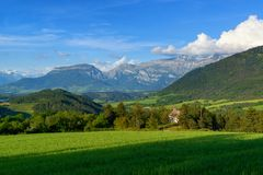 Green meadow and mountains. Rural landscape. Stock Photo