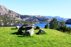 Green meadow in Norway. And stone table and stoll, lake and mountain Stock Photography