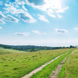 Green meadow with road in mountain and clouds Stock Images