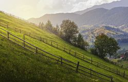 Green meadow and rustic fences. Countryside landscape with rustic wooden fences across green pastures in Magura village, Brasov county, Transylvania, Romania stock image