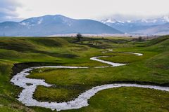 Green meadow with a small river against the background of snow-capped mountains. Winding mountain river royalty free stock images