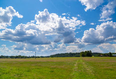 Green meadow under sky with clouds Stock Photo