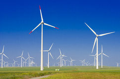 Green meadow with wind turbines stock images
