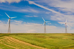 Green meadow with Wind turbines generating electricity.  royalty free stock photo