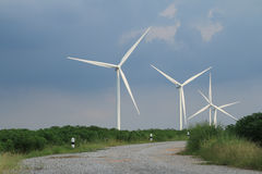 Green meadow with Wind turbines generating electricity. Clouds background royalty free stock photo