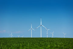 Green meadow with wind turbines generating electricity. Green field with wind turbines generating electricity stock photos