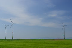 Green meadow with Wind turbines generating electricity. Meadow with Wind power turbines generating electricity royalty free stock photo