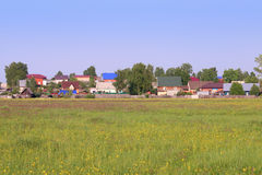 Green meadow with yellow wildflowers and houses in village Stock Photos