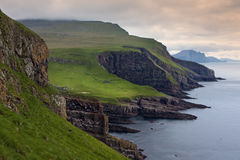 Green meadows and giant sea cliffs overlooking the ocean Stock Image