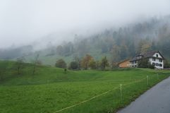 Misty morning in Swiss alps village. Green meadows. Trees in slopes. Alps village in Switzerland stock photography
